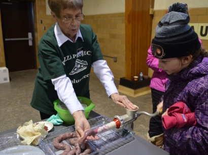 One of the eight stations the children got to visit was the sausage station, where Sam Milne, of Edgewater Park Public School, got to help turn a crank to make sausages. (Amy Hadley/CBC)